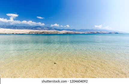 Beautiful mediterranean beach, mountains in the background and the sea