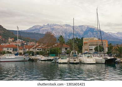 Beautiful Mediterranean landscape on cloudy winter day.   Montenegro, Bay of Kotor. View of Marina Kalimanj in Tivat city and peaks of Lovcen mountains