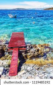 Beautiful Mediterranean sea, Solta, Croatia. Summer vacation. Springboard, turquoise water and little boat. Vivid photo filter.