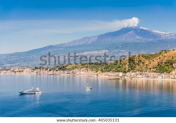 Beautiful mediterranean sicilian coastal landscape with cruising boats view from Taormina with the mount Etna in the background, Sicily, Italy