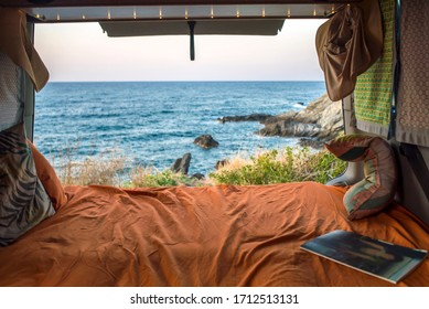 beautiful mediterranean view from a cozy bohemian camper van interior. Unmade bed, pillows, van life theme. Vanlife lifestyle and travel concept/ young people traveling with camper/ restored vehicle