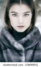 Beautiful melancholic girl wearing mink fur coat