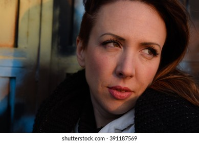 beautiful melancholic woman looking away over the shoulder close-up sunset outside