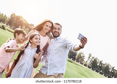 Beautiful memories. Family of four taking selfie photo on smartphone in sunshine smiling happy