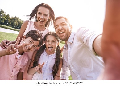 Beautiful memories. Family of four taking selfie photo on smartphone in sunshine smiling happy close-up