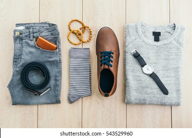 Beautiful men fashion with Sweater Jeans Belt Socks Wallet Watch and Brown leather shoes on wooden background - Vintage light filter Processing