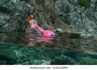 Beautiful mermaid with long tail on sea shore