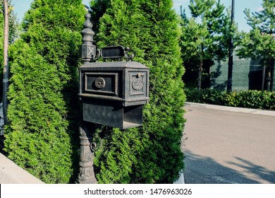 Beautiful metal black mail post box decorated with black ornate designs of wrought iron in vintage style close up near entrance to country house.