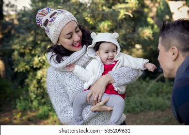 Beautiful mexican couple with a 4 months old baby girl, in winter