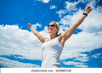 Beautiful mid 30s carefree woman with arms outstretched against a blue sky on a sunny day