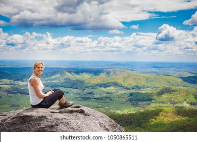 Beautiful mid 30s hiker woman sitting on a rock relaxing on the Old Rag Mountain trail in Shenandoah Valley National Park in Virginia