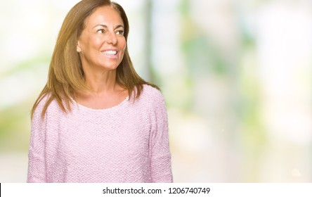 Beautiful middle age adult woman wearing winter sweater over isolated background looking away to side with smile on face, natural expression. Laughing confident.