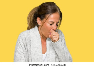 Beautiful middle age adult woman wearing winter sweater over isolated background feeling unwell and coughing as symptom for cold or bronchitis. Healthcare concept.