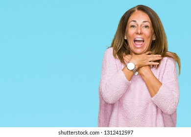 Beautiful middle age adult woman wearing winter sweater over isolated background shouting and suffocate because painful strangle. Health problem. Asphyxiate and suicide concept.