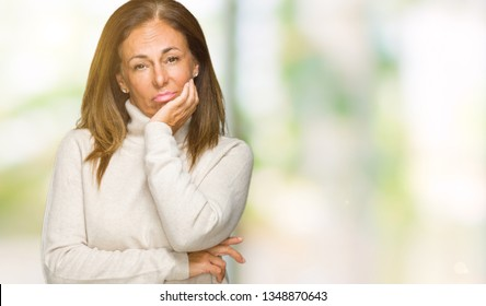 Beautiful middle age adult woman wearing winter sweater over isolated background thinking looking tired and bored with depression problems with crossed arms.