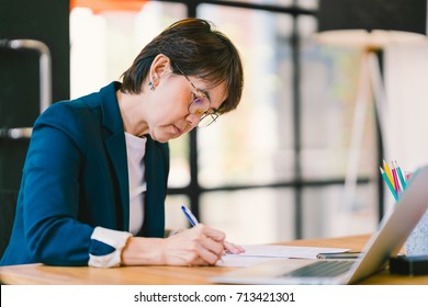 Beautiful middle age Asian woman working on paperwork, sitting in modern contemporary office, with laptop computer. Business owner, entrepreneur, executive manager, or employee office worker concept