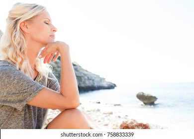 Beautiful middle age blond woman relaxing on a rocky beach by the sea with eyes closed on a sunny holiday destination, textured nature outdoors. Healthy living, wellness recreation lifestyle.