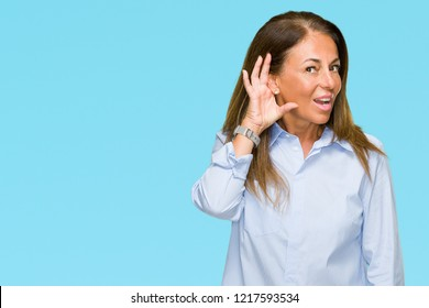 Beautiful middle age business adult woman over isolated background smiling with hand over ear listening an hearing to rumor or gossip. Deafness concept.