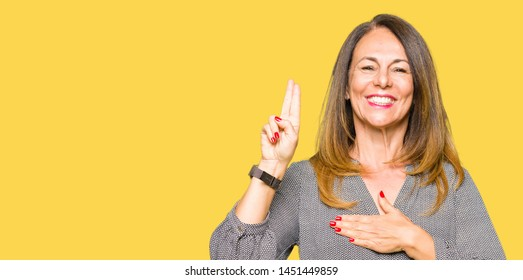 Beautiful middle age business woman Swearing with hand on chest and fingers, making a loyalty promise oath