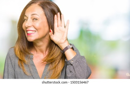 Beautiful middle age business woman smiling with hand over ear listening an hearing to rumor or gossip. Deafness concept.