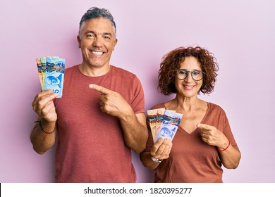 Beautiful middle age couple holding canadian dollars smiling happy pointing with hand and finger