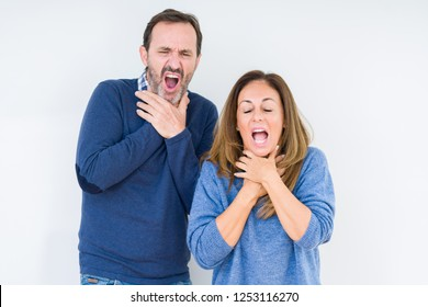 Beautiful middle age couple in love over isolated background shouting and suffocate because painful strangle. Health problem. Asphyxiate and suicide concept.