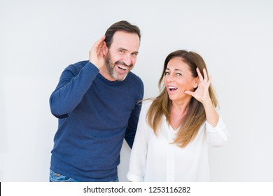 Beautiful middle age couple in love over isolated background smiling with hand over ear listening an hearing to rumor or gossip. Deafness concept.