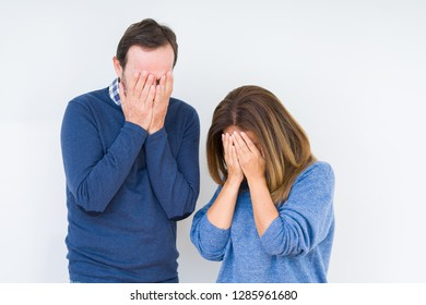 Beautiful middle age couple in love over isolated background with sad expression covering face with hands while crying. Depression concept.