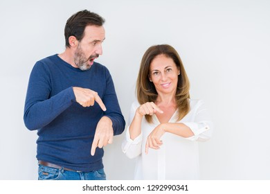 Beautiful middle age couple in love over isolated background In hurry pointing to watch time, impatience, upset and angry for deadline delay