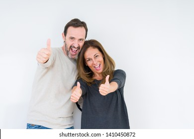 Beautiful middle age couple in love over isolated background approving doing positive gesture with hand, thumbs up smiling and happy for success. Looking at the camera, winner gesture.