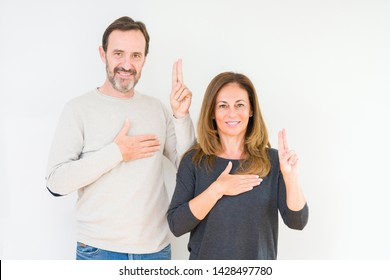 Beautiful middle age couple in love over isolated background Swearing with hand on chest and fingers, making a loyalty promise oath