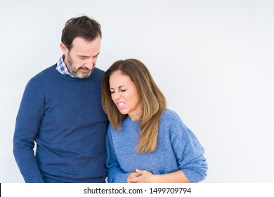 Beautiful middle age couple in love over isolated background with hand on stomach because indigestion, painful illness feeling unwell. Ache concept.