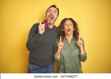 Beautiful middle age couple over isolated yellow background amazed and surprised looking up and pointing with fingers and raised arms.