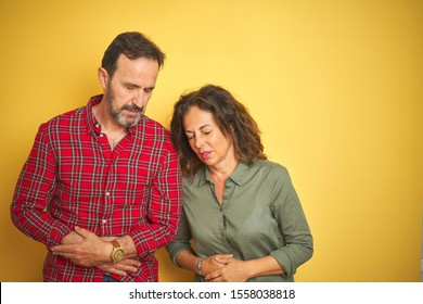 Beautiful middle age couple over isolated yellow background with hand on stomach because indigestion, painful illness feeling unwell. Ache concept.