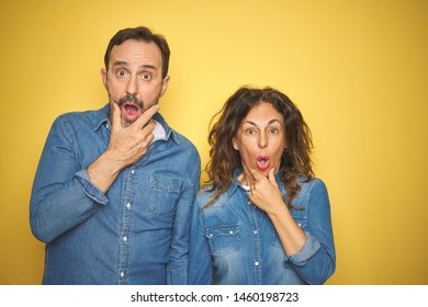 Beautiful middle age couple together standing over isolated yellow background Looking fascinated with disbelief, surprise and amazed expression with hands on chin