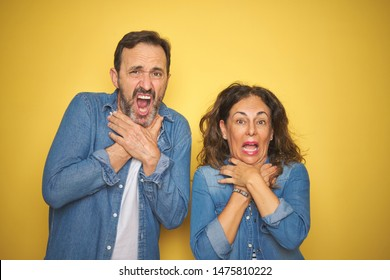 Beautiful middle age couple together wearing denim shirt over isolated yellow background shouting and suffocate because painful strangle. Health problem. Asphyxiate and suicide concept.