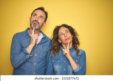 Beautiful middle age couple together standing over isolated yellow background Thinking concentrated about doubt with finger on chin and looking up wondering