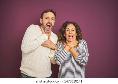 Beautiful middle age couple wearing winter sweater over isolated purple background shouting and suffocate because painful strangle. Health problem. Asphyxiate and suicide concept.