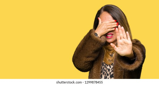 Beautiful middle age elegant woman wearing mink coat covering eyes with hands and doing stop gesture with sad and fear expression. Embarrassed and negative concept.