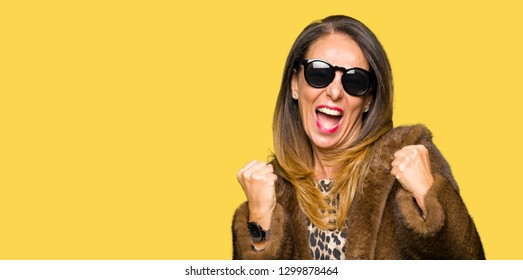 Beautiful middle age elegant woman wearing sunglasses and mink coat very happy and excited doing winner gesture with arms raised, smiling and screaming for success. Celebration concept.