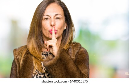 Beautiful middle age elegant woman wearing mink coat asking to be quiet with finger on lips. Silence and secret concept.