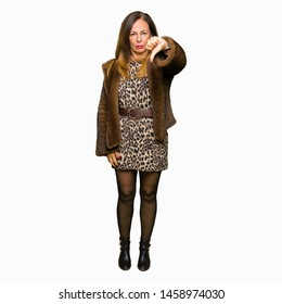 Beautiful middle age elegant woman wearing mink coat looking unhappy and angry showing rejection and negative with thumbs down gesture. Bad expression.