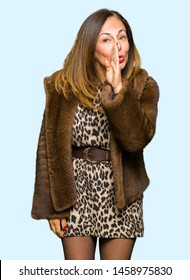 Beautiful middle age elegant woman wearing mink coat hand on mouth telling secret rumor, whispering malicious talk conversation