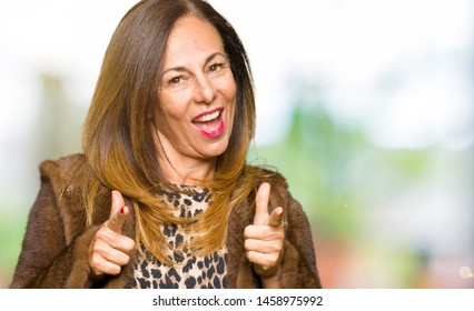 Beautiful middle age elegant woman wearing mink coat pointing fingers to camera with happy and funny face. Good energy and vibes.
