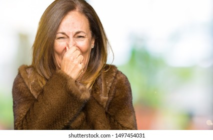 Beautiful middle age elegant woman wearing mink coat smelling something stinky and disgusting, intolerable smell, holding breath with fingers on nose. Bad smells concept.