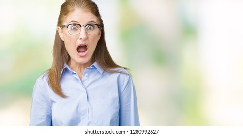 Beautiful middle age mature business woman wearing glasses over isolated background In shock face, looking skeptical and sarcastic, surprised with open mouth