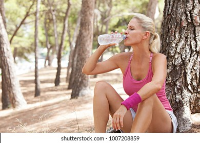 Beautiful middle age sporty woman resting from exercising in nature park, sitting drinking mineral water bottle with eyes closed. Fitness, wellness and well being, sport activities. Training outdoors.