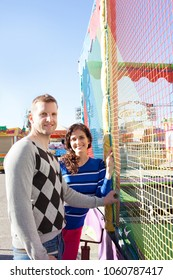 Beautiful middle age tourist couple joyfully smiling looking at camera in a colorful amusement park, outdoors. Funfair theme park with festival attraction rides, leisure recreation lifestyle.