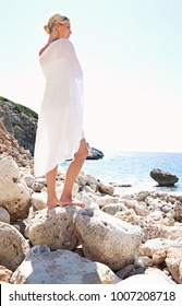 Beautiful middle age tourist woman standing on textured rocks beach with white silk fabric wrapped around body, contemplative in nature, outdoors. Healthy free female, well being recreation lifestyle.