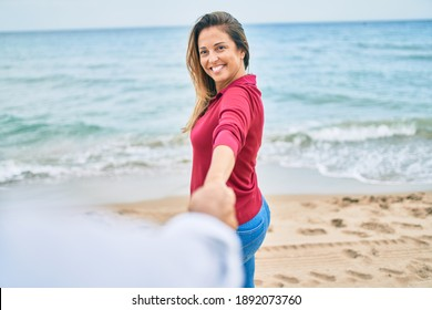 Beautiful middle age woman holding hands with husband at the beach, leading the way happy smiling in love